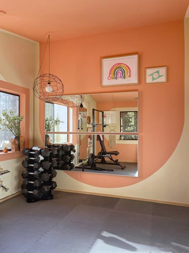pink and white accent wall with artwork in home gym