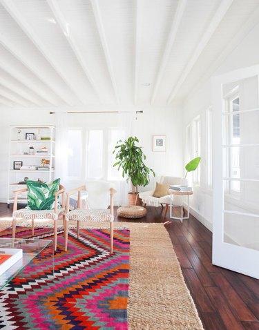 colorful patterned rug over natural fiber rug in living room