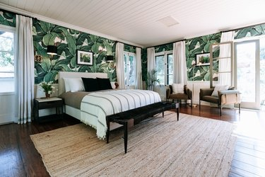 A bedroom with palm leaf wallpaper and floor length drapes