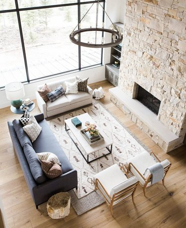 graphic patterned area rug on top of neutral area rug in great room