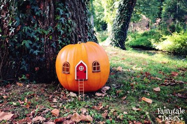 outdoor area with tree and pumpkin decorated to look like a tiny house