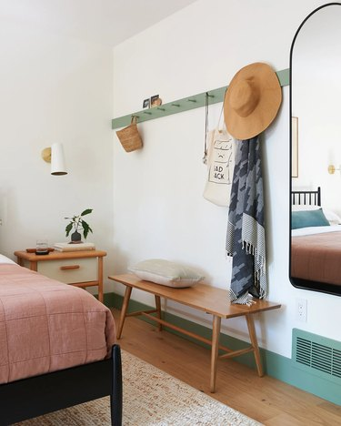green wall hooks in small bedroom