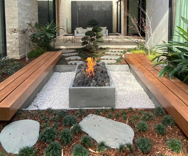 A garden with two wooden benches and a gravel patio with a concrete fire pit on top