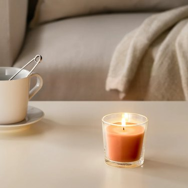 orange candle on table near mug and couch in the background