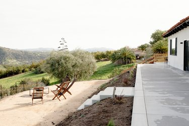 Concrete walkway with steps leading down to a dirt patio area where there are four wooden lounge chairs and a fire pit. The seating area overlooks rolling hills and a young vineyard.