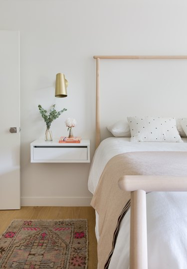 small white bedroom with brass sconce