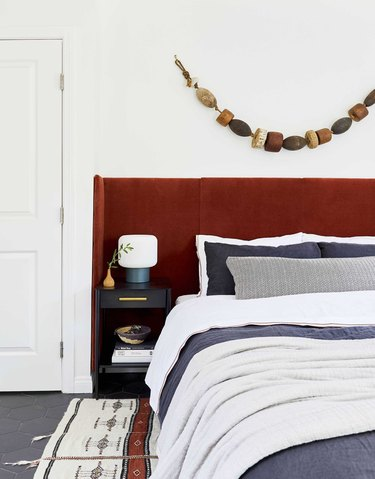 small bedroom with red velvet headboard and vintage buoy wall art