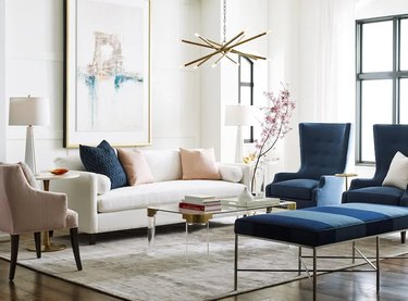living room with white couch, large artwork, and blue chairs