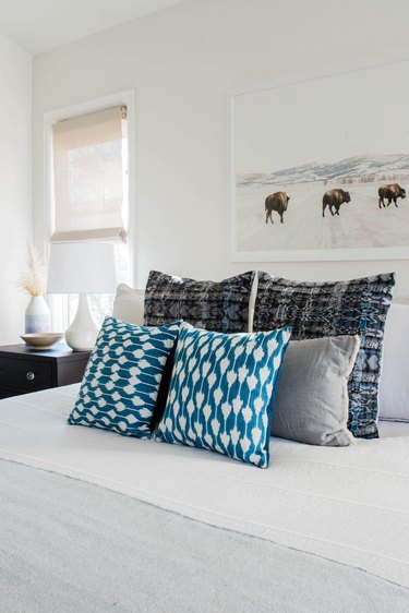 white bed with blue throw pillows in small bedroom