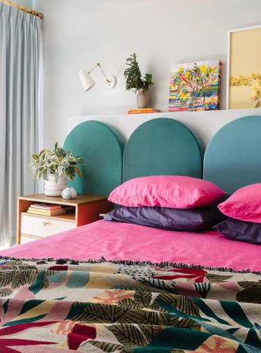 colorful small bedroom with arched headboard