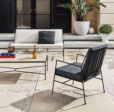 outdoor seating area with white couch and black chair