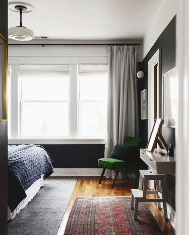small bedroom with vintage rug and green velvet chair
