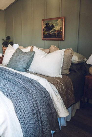 small green bedroom with vintage wall art