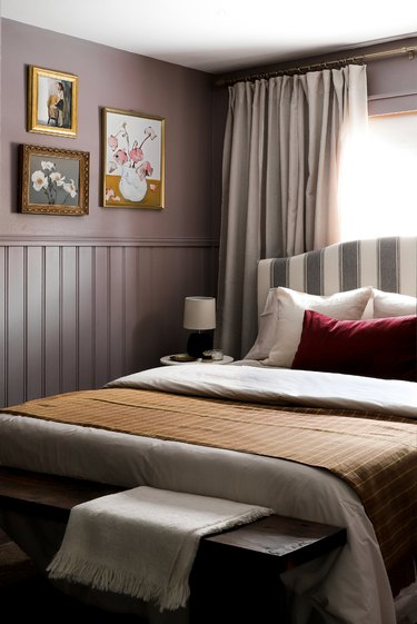 small purple bedroom with vintage art gallery wall