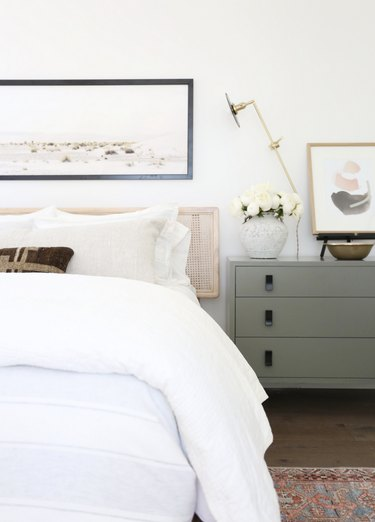 white bed with green dresser in small bedroom