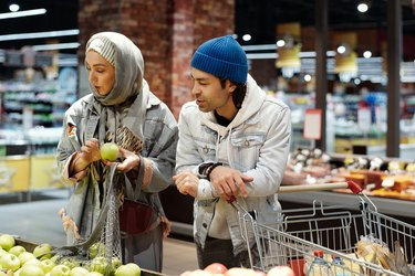 couple buying apples in grocery store