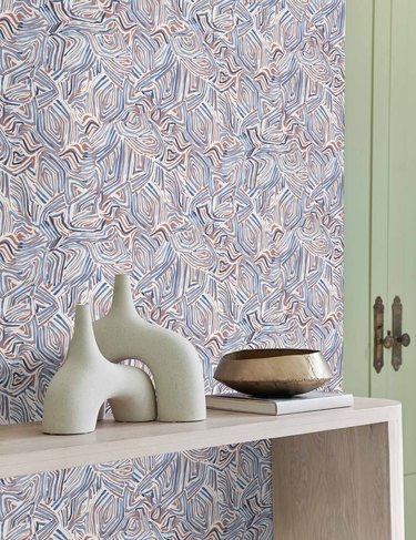 patterned wallpaper with console and ceramics