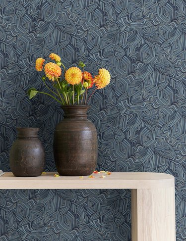 patterned wallpaper with console, vases, and flowers