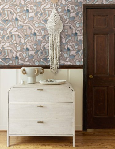 patterned wallpaper with dresser and wall hanging