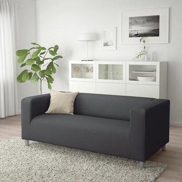 dark gray couch near white furniture and white framed artwork