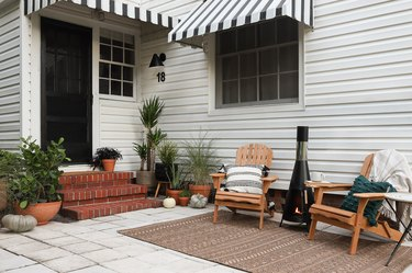 Porch area decorated for fall with outdoor furniture, a fireplace, and plants