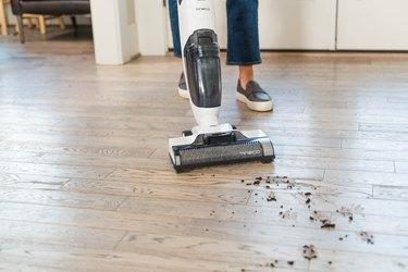 person vacuuming wood floor