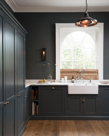 dark blue kitchen with arched window and wooden sliding shutters