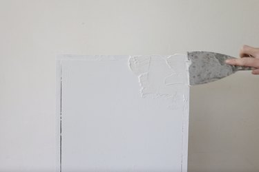 Applying joint compound with putty knife to plinth