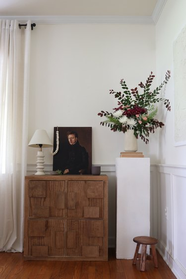 DIY plinth pedestal table stand with flowers next to cabinet