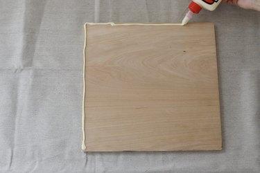Piping wood glue along edge of wood board