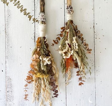 autumn besoms hanging on white wood wall