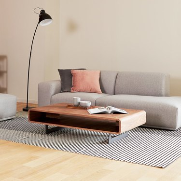 Low rectangular rounded coffee table with one wide open shelve and low metal legs