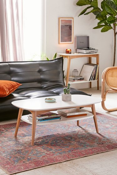 Rounded rectangular wood coffee table with white surface and white lower shelf