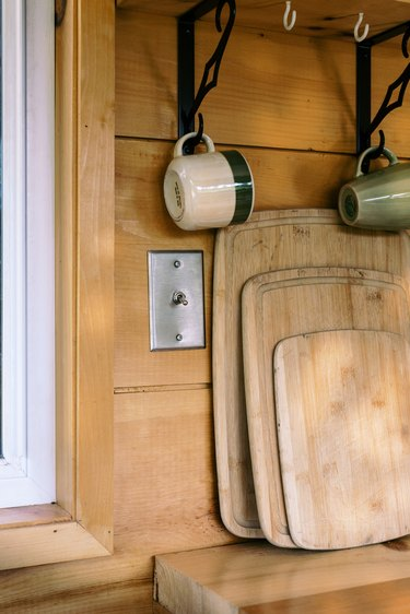 Various cutting boards and hanging cups against wood-paneled wall