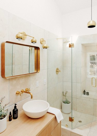 a light, airy bathroom with off-white tile, a blonde wood vanity, and a white raised basin sink