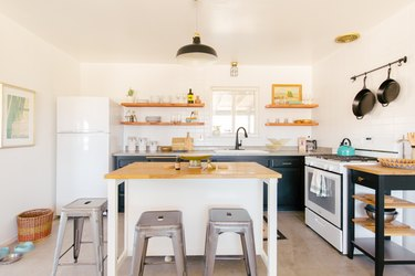 a small island in a large modern kitchen flanked by industrial metal stools