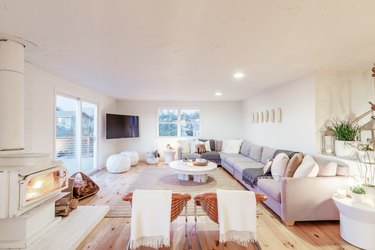 a large airy living room with a very long sectional couch running the length of one wall