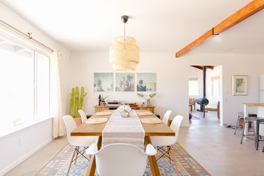 a solid wooden dining table under a large rattan pendant lamp in a spacious open-plan house