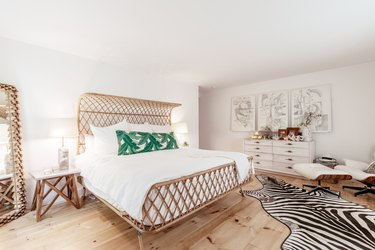 a bed with a rattan frame in a bedroom with pine floors and a zebra-skin rug