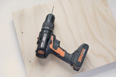 a power drill on a sheet of plywood with several holes drilled in it