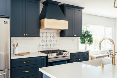 Dark blue kitchen cabinets, ornate backsplash by stovetop, white kitchen island countertop with gold sink faucet.