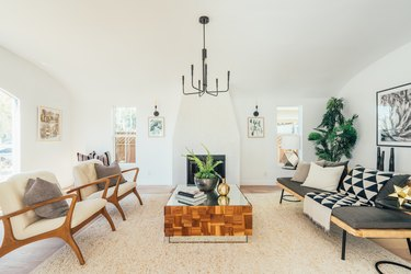 Living room with modernist armchairs, wood and mirrored coffee table, gray upholstered sofa, black industrial chandelier