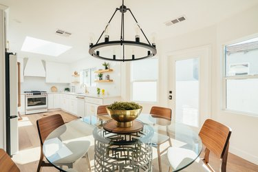 Glass tabletop dining table with modernist wood chairs and a black industrial chandelier