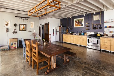 rustic industrial decor in industrial kitchen with wood cabinets and dining table and vintage wall decor
