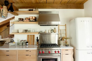 A kitchen with a retro white fridge, wood shelves, wood cabinets, and a red knob stove.