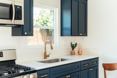 Kitchen with dark cabinets with gold handles and white countertop with single-handle kitchen faucet and a houseplant
