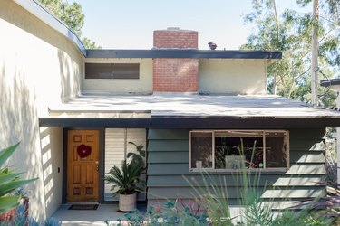 A midcentury modern house with a brick chimney, gray and white exterior, and wood door.