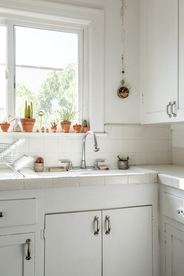 Minimalist kitchen with white cabinets, white tile backsplash, metal faucet sink, and assorted windowsill plants.