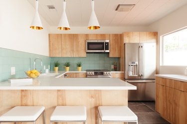 Light wood kitchen cabinets and green backsplash. Yellow planters decorate the counters. Fluted pendant lights and white square stools.