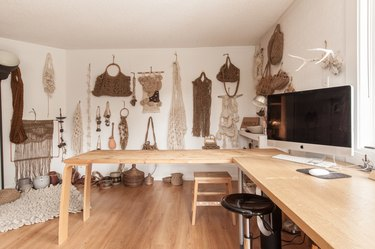 Studio with a display wall of macrame purses and wall hangings. A wood L-shape desk with a computer.